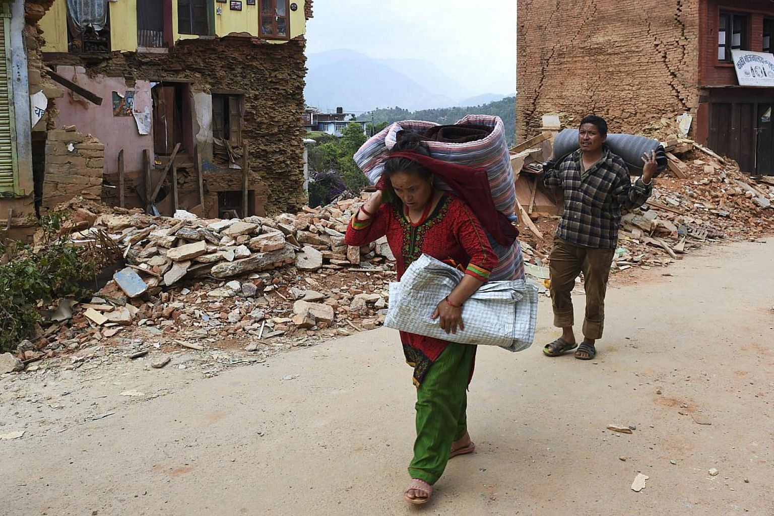 Nepalese residents carry their belongings as they walk past destroyed buildings inthe town of Chautara in north-eastern Nepal in the aftermath of two earthquakes in the span of three weeks that shook the country. -- PHOTO: AFP