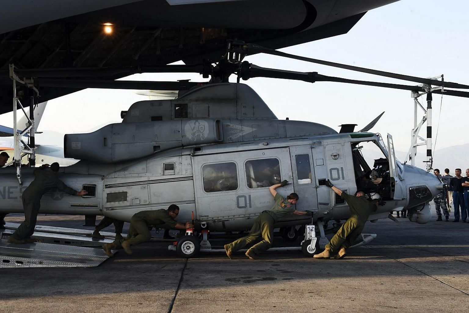 A photo taken on May 3, 2015, shows the crew of a US C-17 military transport plane unloading a Huey helicopter at Kathmandu's international airport in Kathmandu.The US military said Friday it did not expect to find any survivors after locating