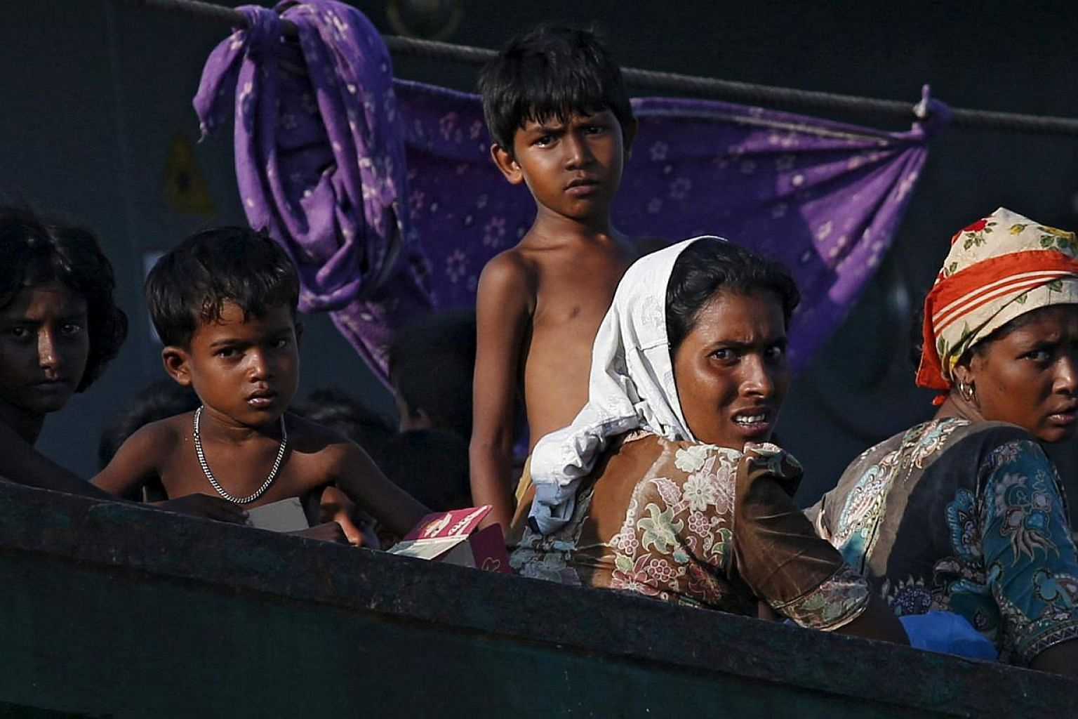 """Migrants looking on while on board a boat tethered to a Thai navy vessel, in waters near Koh Lipe island, on May 16, 2015.Muslim boatpeople fleeing dire conditions in Myanmar are entitled to """"human rights"""", a spokesman for Aung San Suu Kyi's op"""