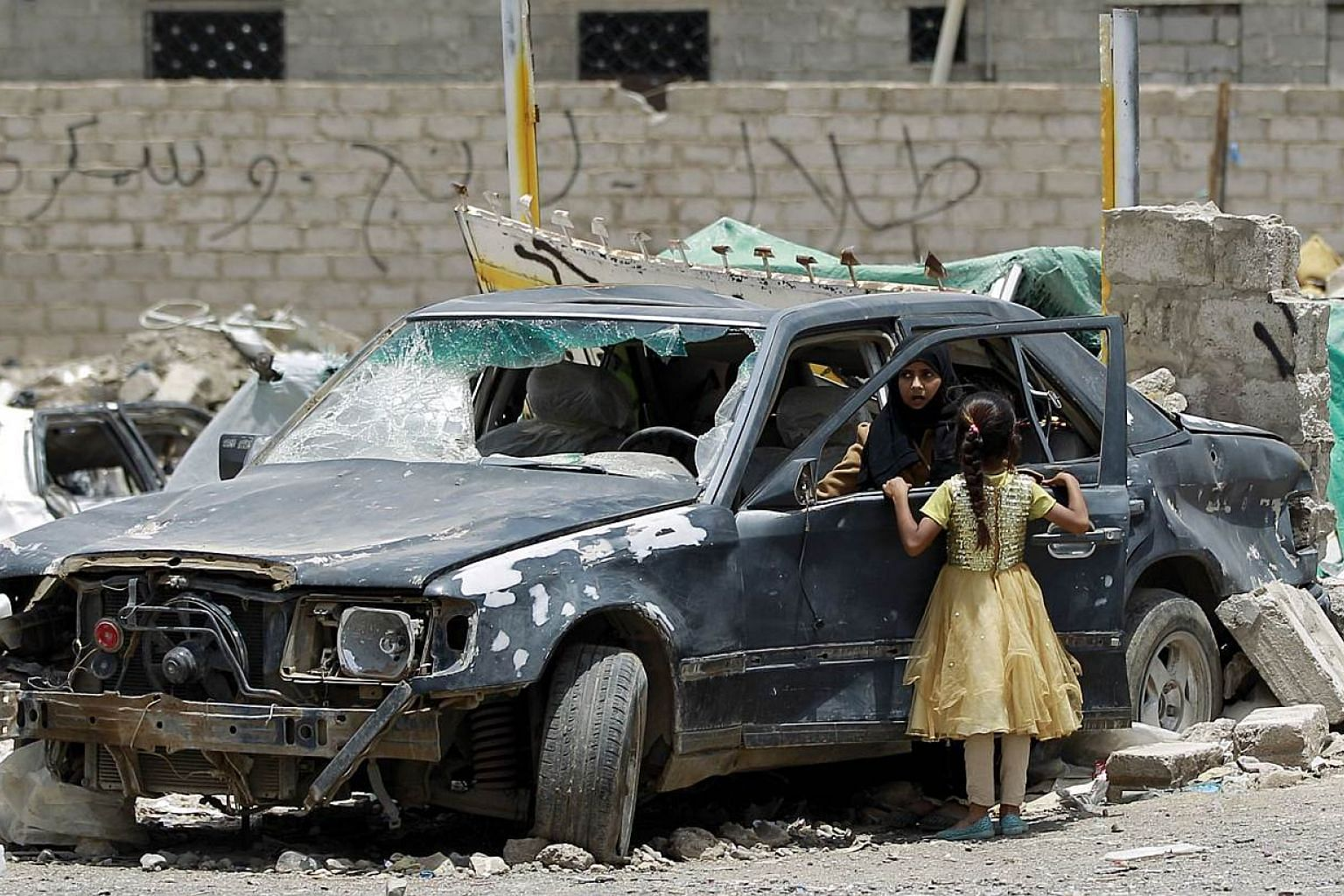 A Yemeni woman inpecting a damaged car in a residential area that was destroyed by Saudi-led air strike last month, in the capital Sanaa, on May 18, 2015. -- PHOTO: AFP