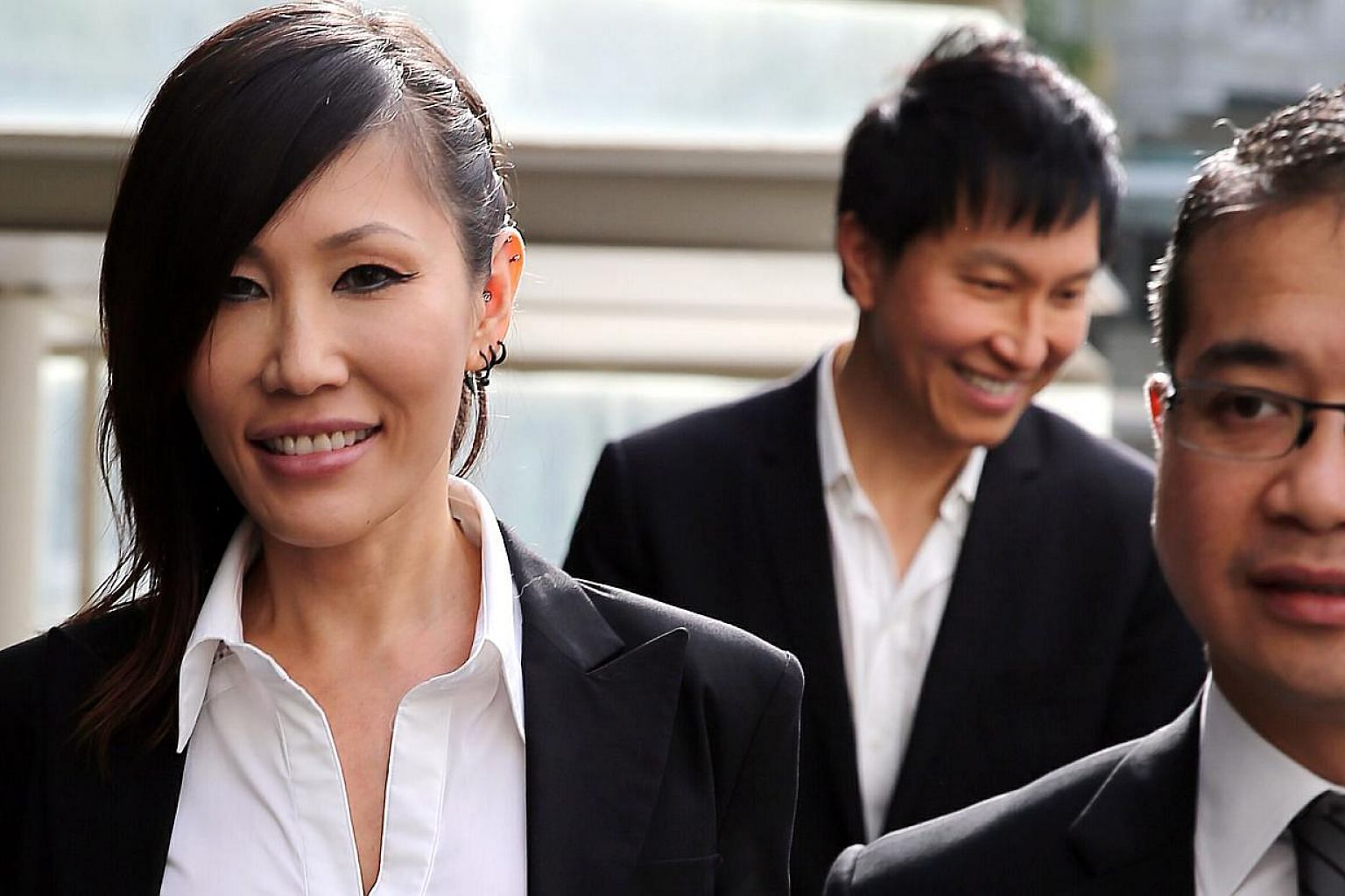 Pop singer Sun Ho (left) arriving at the State Courts on May 19, 2015, with her husband Kong Hee (centre), founder of City Harvest Church, and Senior Counsel Edwin Tong. -- PHOTO: WONG KWAI CHOW