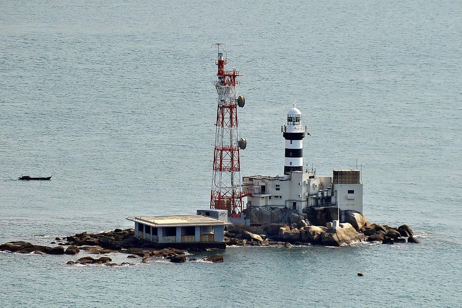 A barge that capsized with 15 crew on board in waters near Pedra Branca lighthouse (pictured) was towed to shore on Thursday, May 21, 2015, even as the search for missing crew members continues.  -- PHOTO: ST FILE