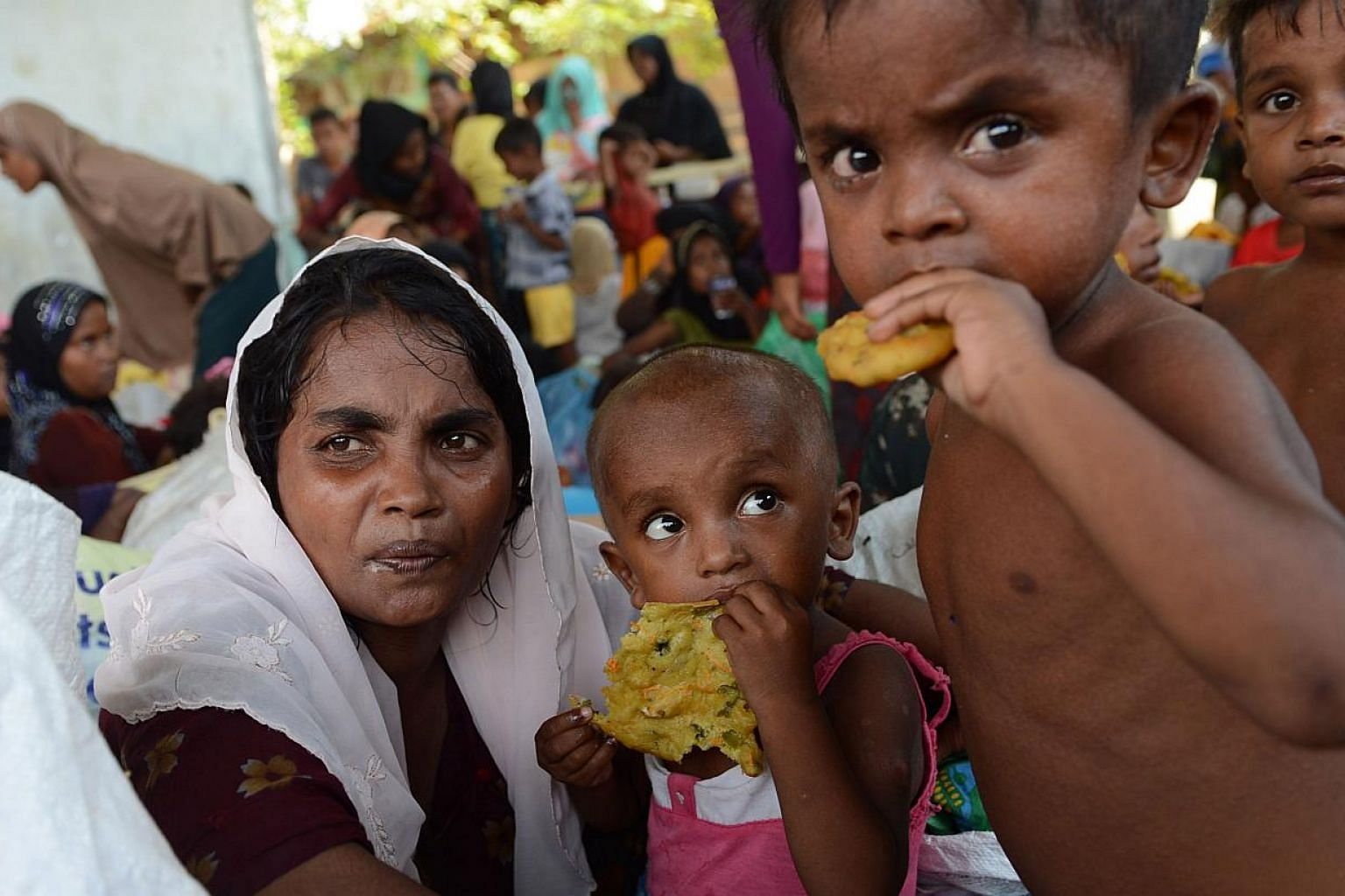 Rescued Rohingya women and children are provided with food by Indonesian residents in the compound of a mosque in Julok district, Aceh province, on May 20, 2015, after they were rescued by Indonesian fishermen off the waters of the eastern coast of A