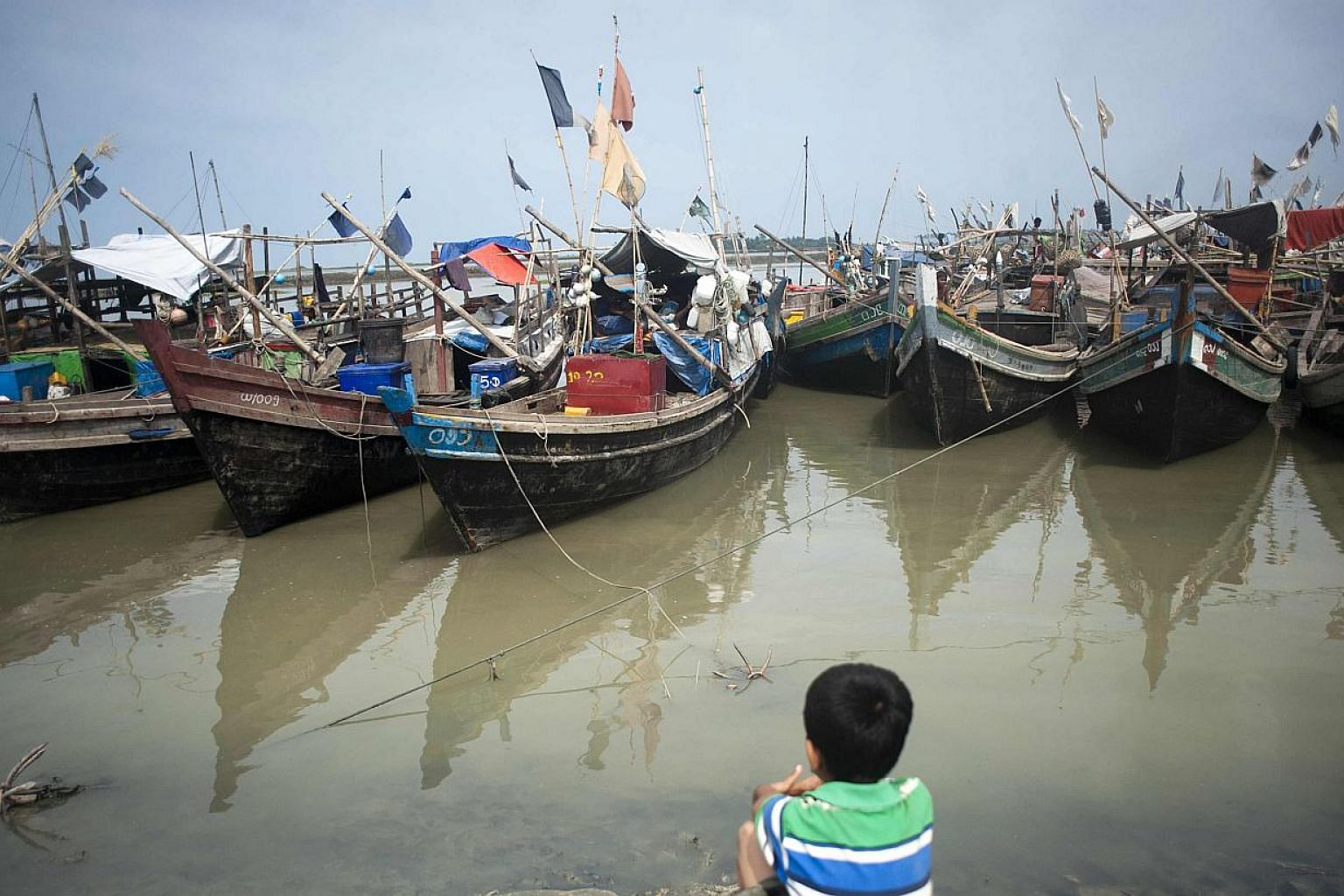 An ethnic Rohingya Muslim child looks at boats near a jetty at a refugee camp outside the city of Sittwe in Myanmar's Rakhine state on May 22, 2015. -- PHOTO: AFP