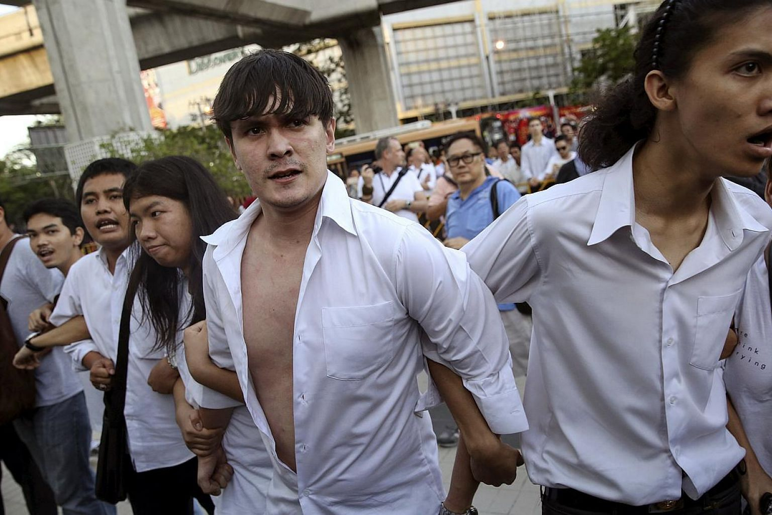 """Thai protesters facing policemen in central Bangkok on May 22, 2015. Dozens of students who were dragged away and held overnight by police after they staged an anti-coup protest in Bangkok on Friday evening were """"merely invited for talks"""", a senior p"""