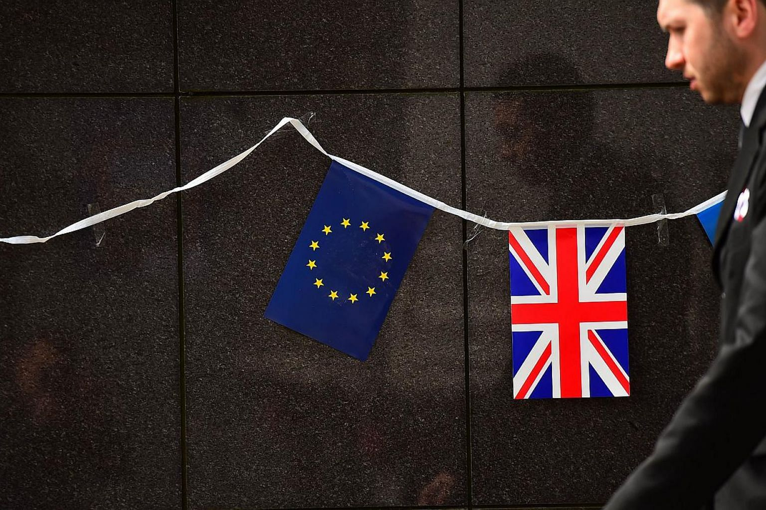 An European flag and a British flag stand next to each other outside the European Commission building in Brussels on May 8 2015. Britain's centre-left opposition Labour party will support Prime Minister David Cameron's proposal for a referendum on Eu