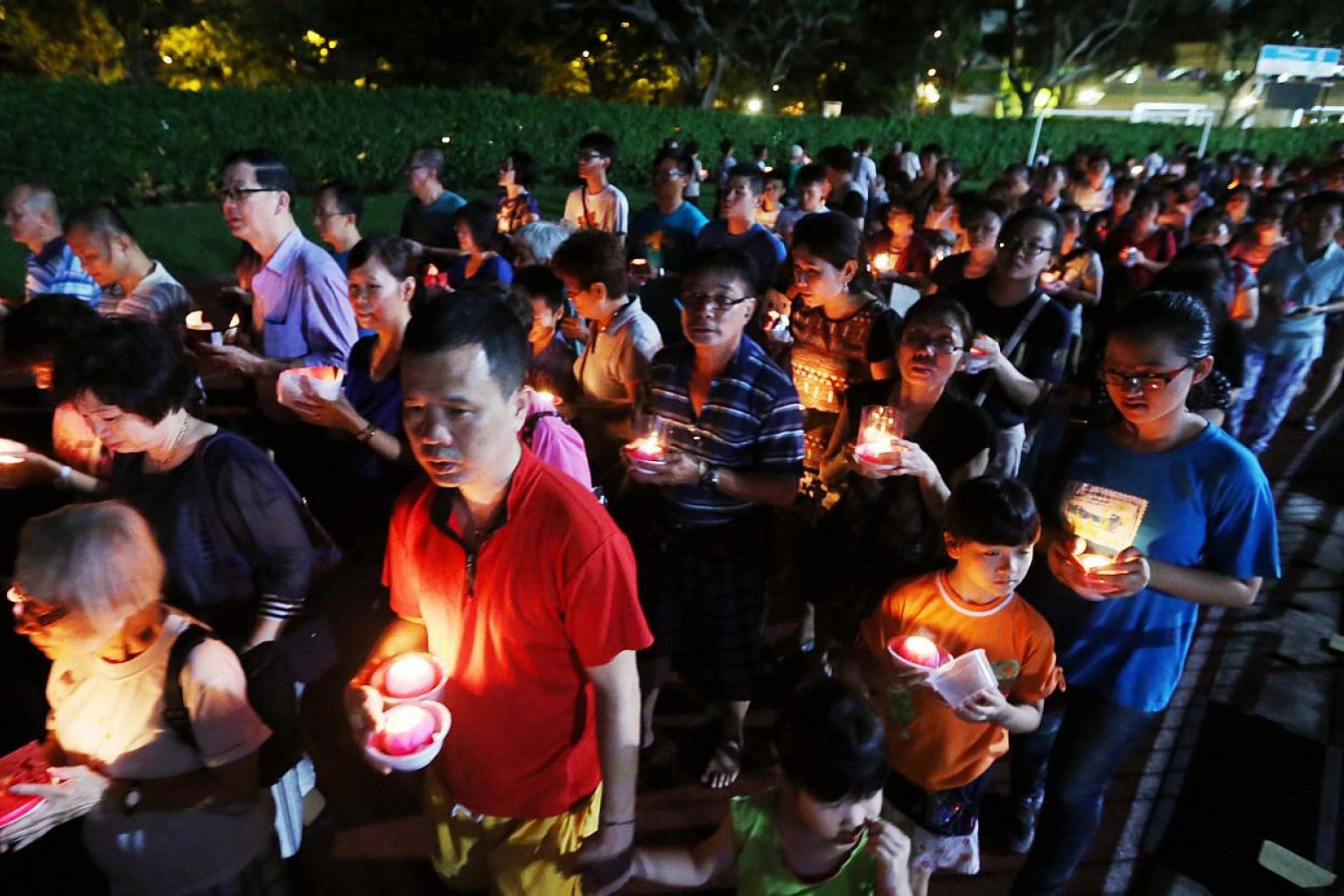 Buddhist devotees holding candles shaped like lotus flowers and praying for peace, at Hougang Stadium on May 24, 2015. -- PHOTO: LIANHE ZAOBAO