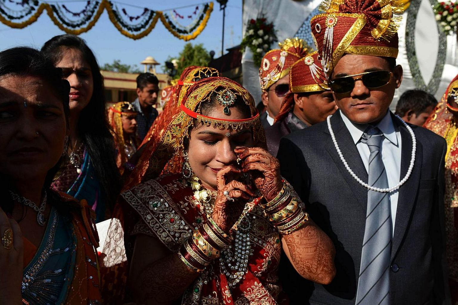 An Indian bride (centre) adjusts her jewellry ahead of a mass wedding in Ahmedabad on May 17, 2015. -- PHOTO: AFP