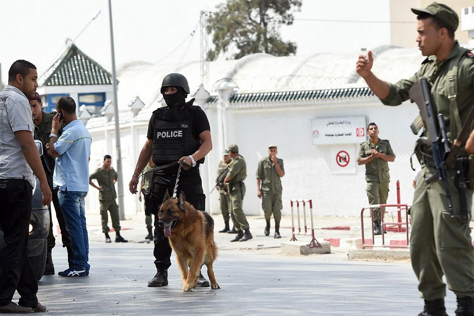 Tunisian soldiers and policemen stand guard outside the Bouchoucha army barracks in Tunis on May 25, 2015 after a soldier opened fire at his colleagues. -- PHOTO: AFP