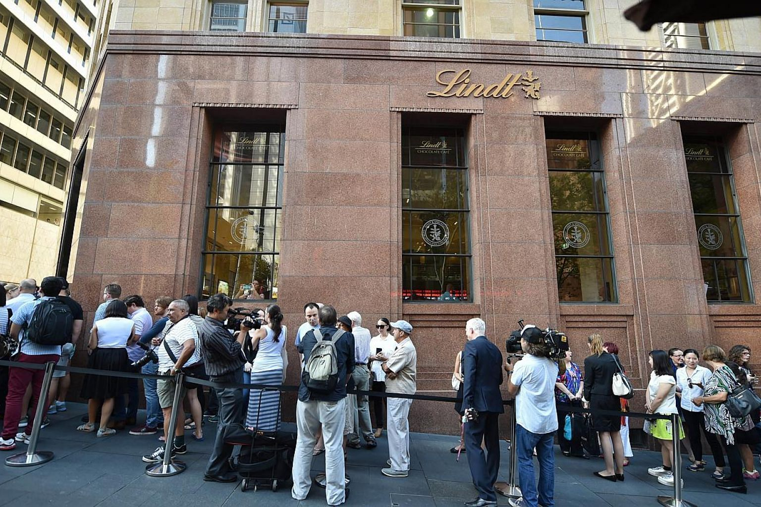 """Members of the public queue outside the Lindt Cafe at Martin Place in Sydney ahead of the re-opening on March 20, 2015.A self-styled sheikh who staged a siege at the cafe last year suffered """"grandiose delusions"""" and was once kicked out of"""