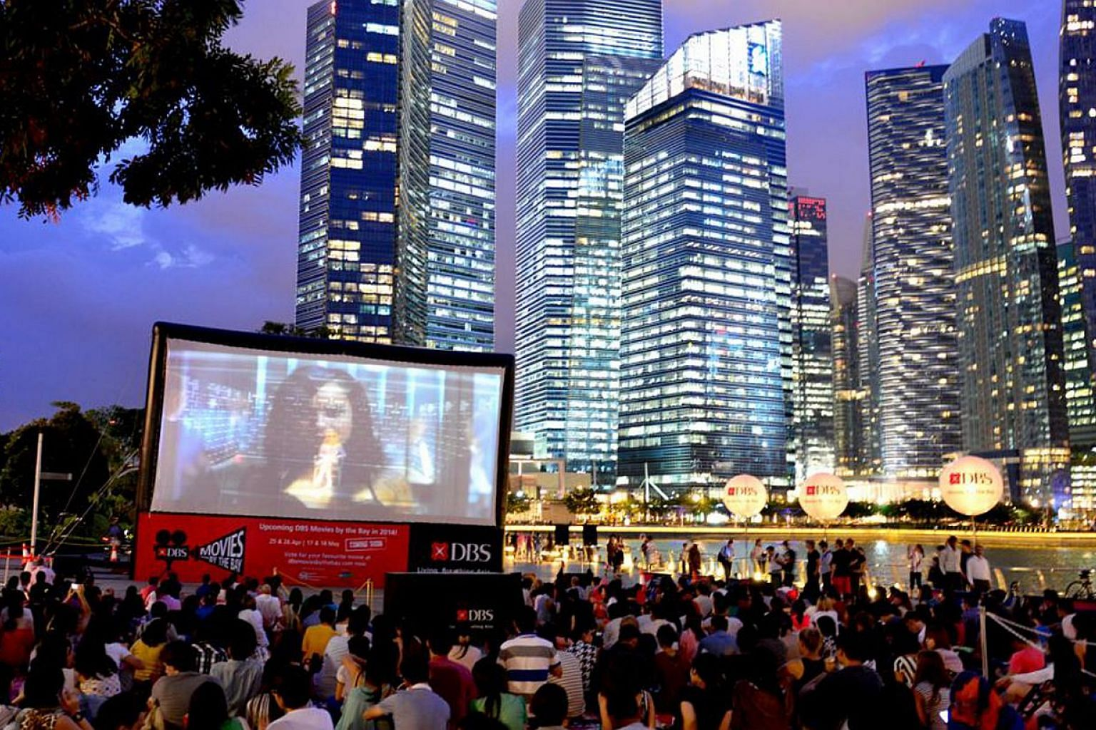 People watching a film during a screening at the DBS Movies by the Bay, a monthly event launched in October 2013. DBS has pledged to pump in another $12 million over the next three years to draw more people to the Marina Bay area, to make it a vibran