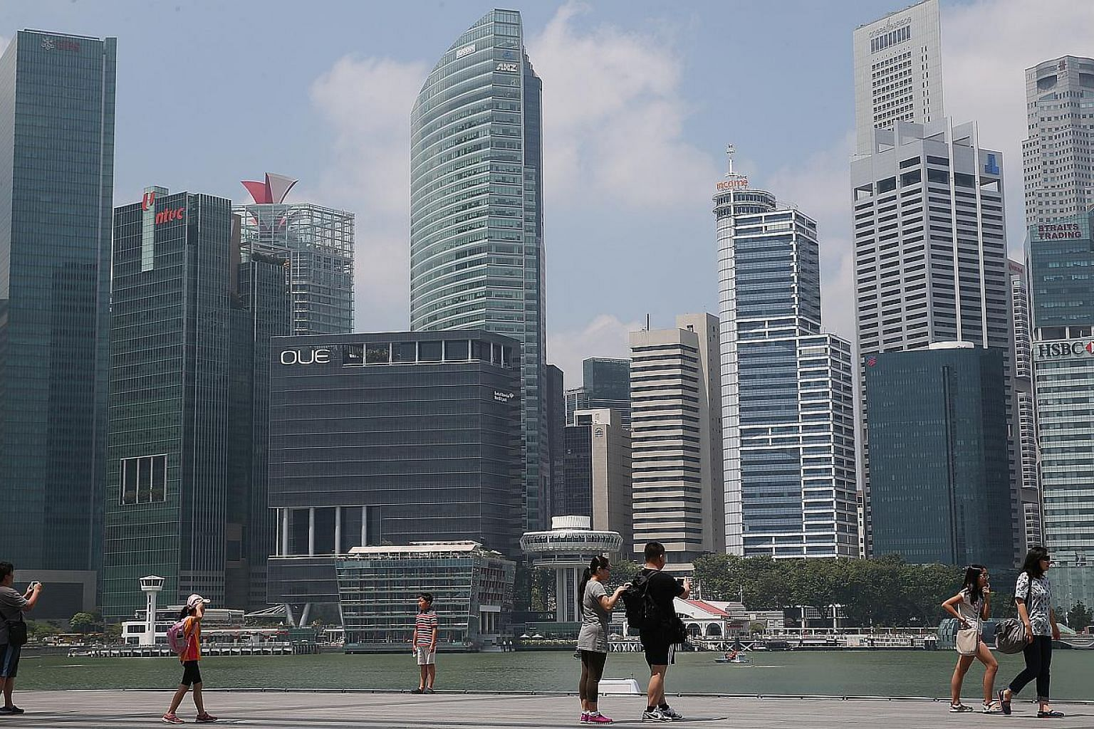 Tourists walking along the path on the waterfront promenade, along Marina Bay Sands as the skyline of Singapore Central Business District (CBD) stands in the background. The Singapore economy grew a moderate 2.6 per cent in the first three months of