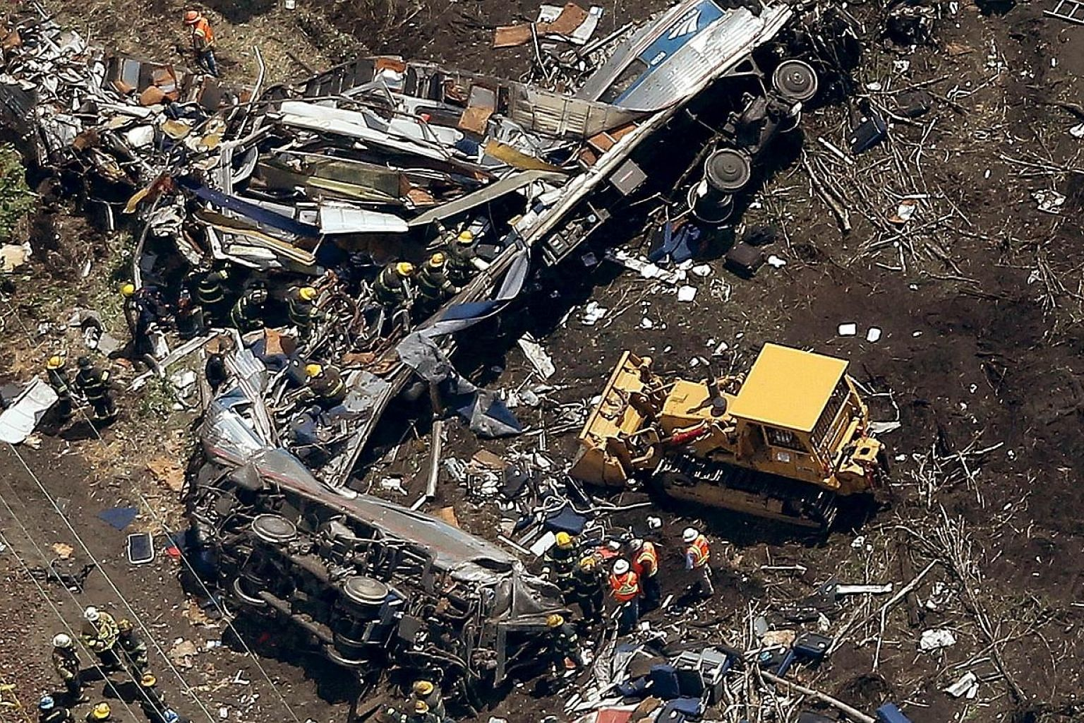 Investigators and first responders work near the wreckage of an Amtrak passenger train carrying more than 200 passengers from Washington, DC to New York that derailed late last night May 13 in north Philadelphia, Pennsylvania. At least five people we