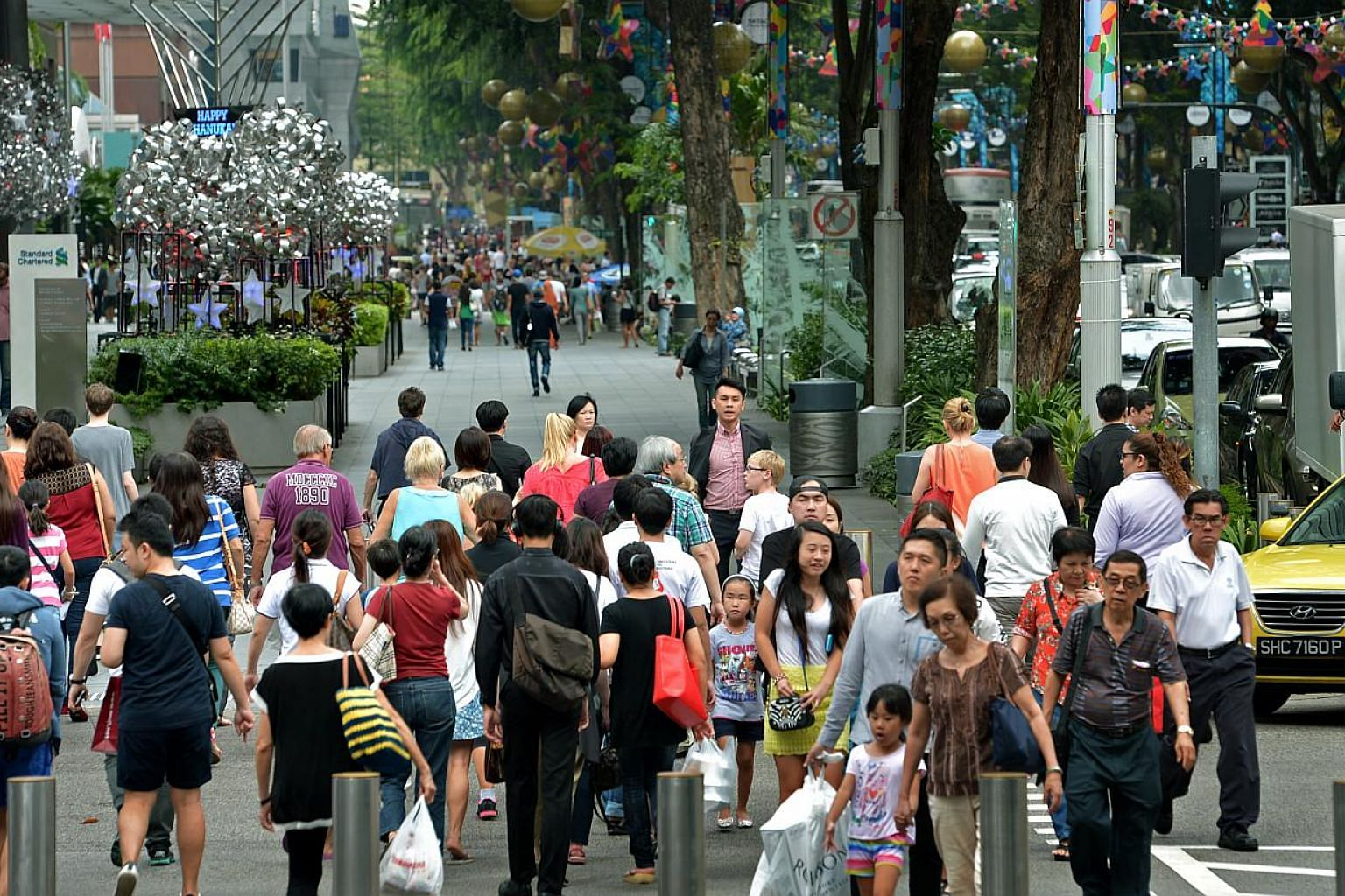 Shoppers along Orchard Road near the junction of Takashimaya. Consumer confidence in Singapore continued to climb in May, with respondents in a survey more upbeat about both their current and future financial state. -- PHOTO: ST FILE