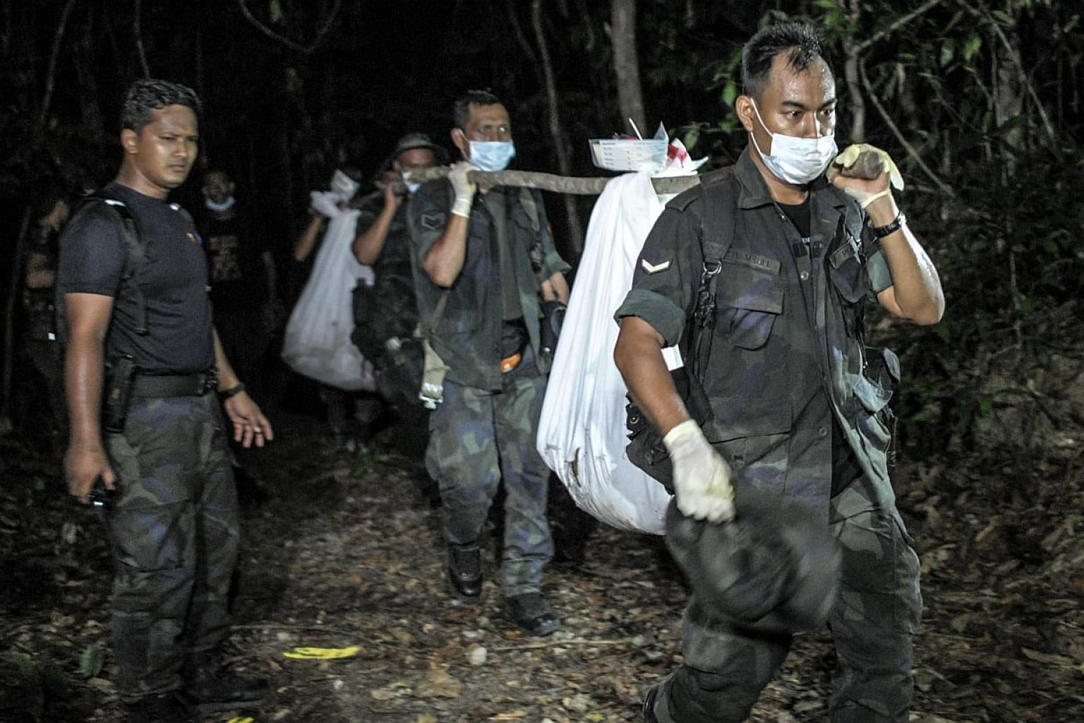 Royal Malaysian Police personnel carry exhumed human remains recovered from the jungle in the Malaysian northern state of Perlis, which borders Thailand, in Wang Kelian on May 28, 2015. -- PHOTO: AFP