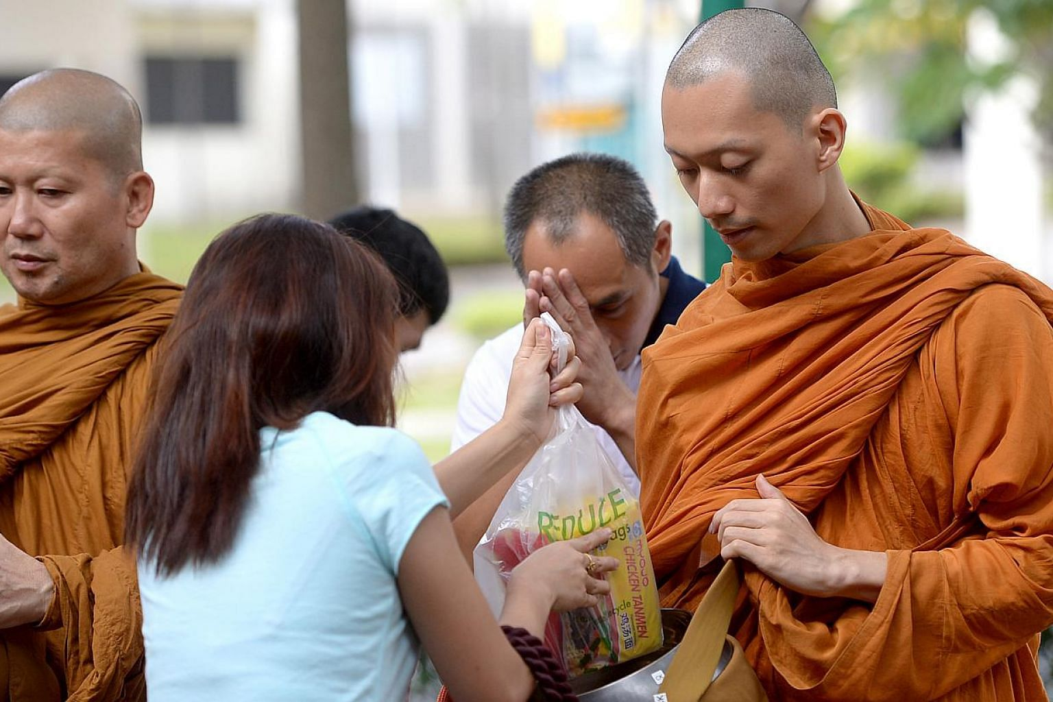 Venerable Goh Chun Kiang collecting cooked food from people at a food centre. The food is then distributed as lunch to the monks and lay people at Palelai Buddhist Temple. -- ST PHOTO: JAMIE KOH