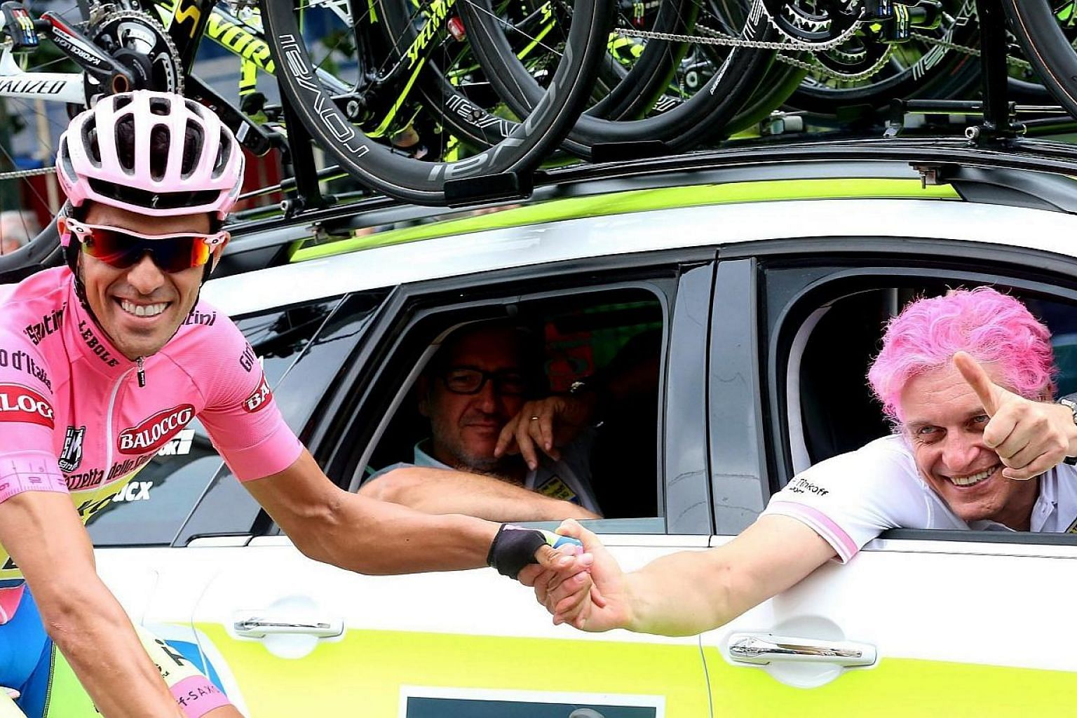 Spanish rider Alberto Contador (left) of the Tinkoff-Saxo team and Russian businessman and team owner Oleg Tinkov, with his hair painted in pink to match the overall leader's jersey,on the way to the 21st and last stage of the 98th Giro d