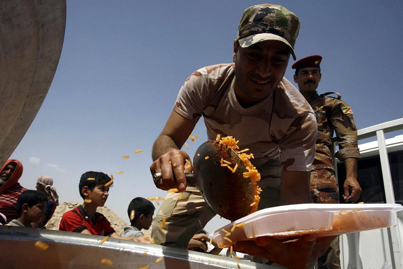 A member of the Iraqi government forces distributes food to displaced Iraqis who fled Anbar province due to the ongoing conflict between pro-government forces and Islamic State (IS) group jihadists, at a makeshift camp for internally displaced person