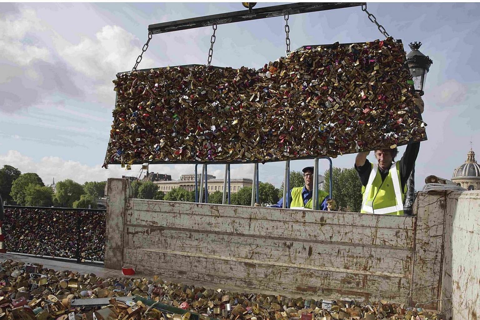 """City municipal employees lower iron grills covered with """"love locks"""" into a truck after they were removed from the Pont des Arts in Paris, France, on June 1, 2015. Parisian authorities on Monday removed tens of thousands of """"love locks"""", padlocks cha"""