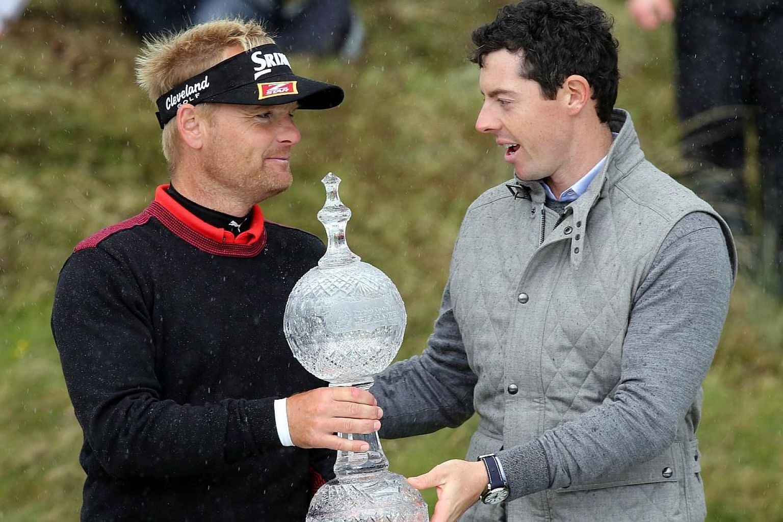 Soren Kjeldsen (left) of Denmark is handed the trophy by Northern Ireland's Rory McIlroy after winning the Irish open at the Royal County Down Golf Club in Newcastle in Northern Ireland on Sunday (May 31). -- PHOTO: AFP