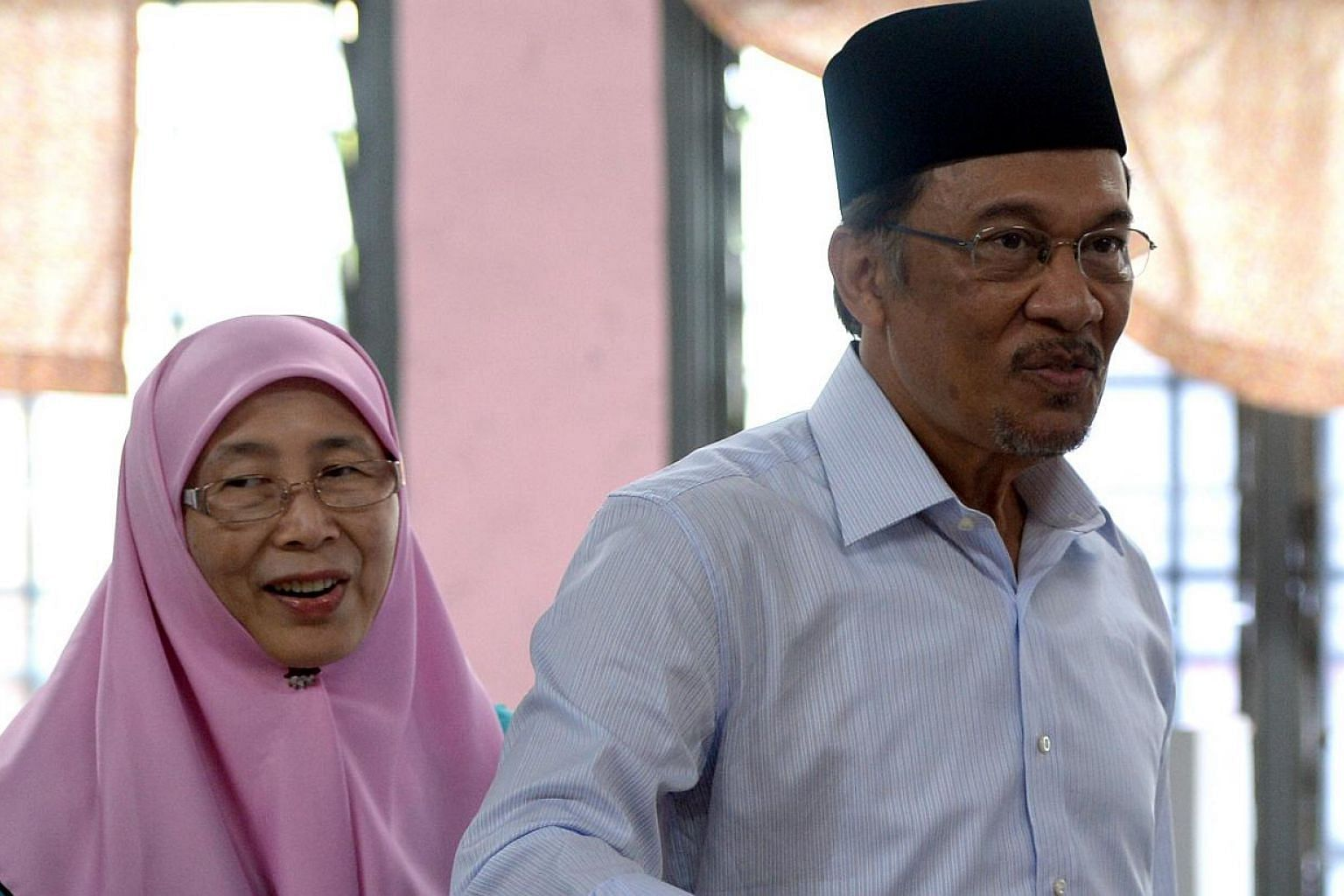 In this file photo taken on May 5, 2013, opposition leader Anwar Ibrahim (right), accompanied by his wife Wan Azizah, casts his vote at a polling station in Permatang Pauh, Penang. -- PHOTO: AFP