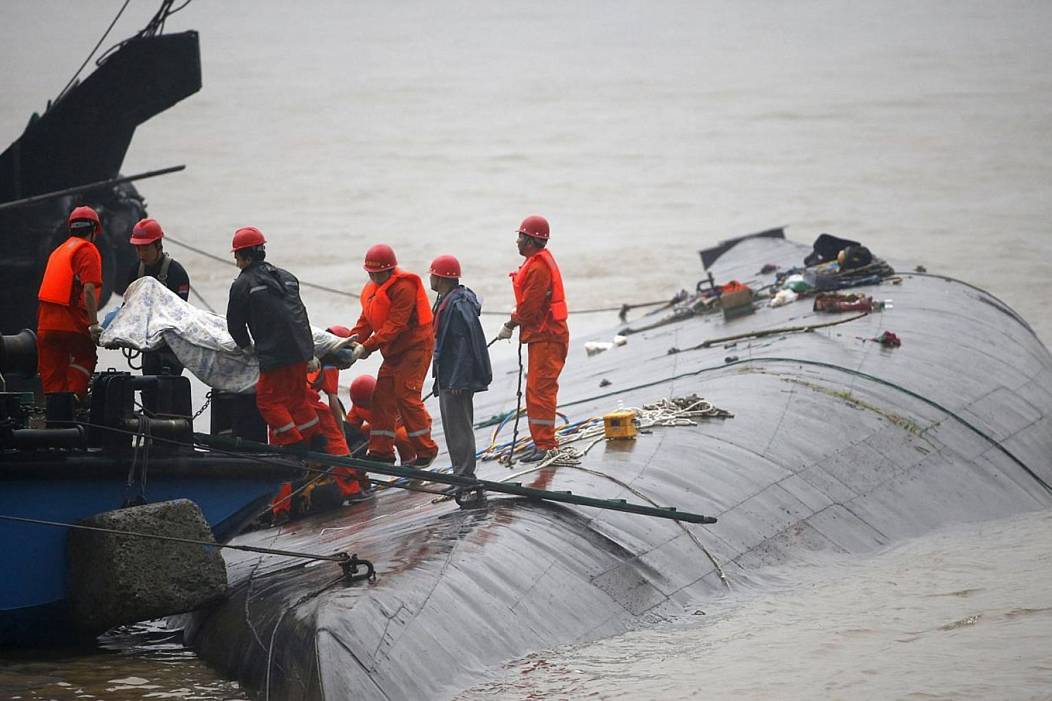 Rescue workers carry a body from a sunken ship in the Jianli section of Yangtze River, Hubei province, China, on June 2, 2015. The sinking of the cruise boat is likely to mar the country's generally clean maritime safety record, which hasn't suffered