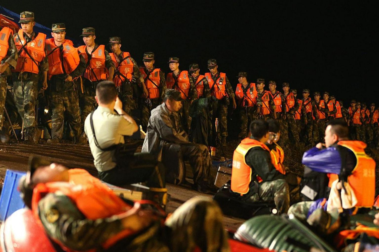 Rescuers walk in a line along the bank side of the Yangtze River as they search for missing passengers of a capsized tourist ship in Jianli, Hubei province, China, on June 2, 2015. -- PHOTO: EPA
