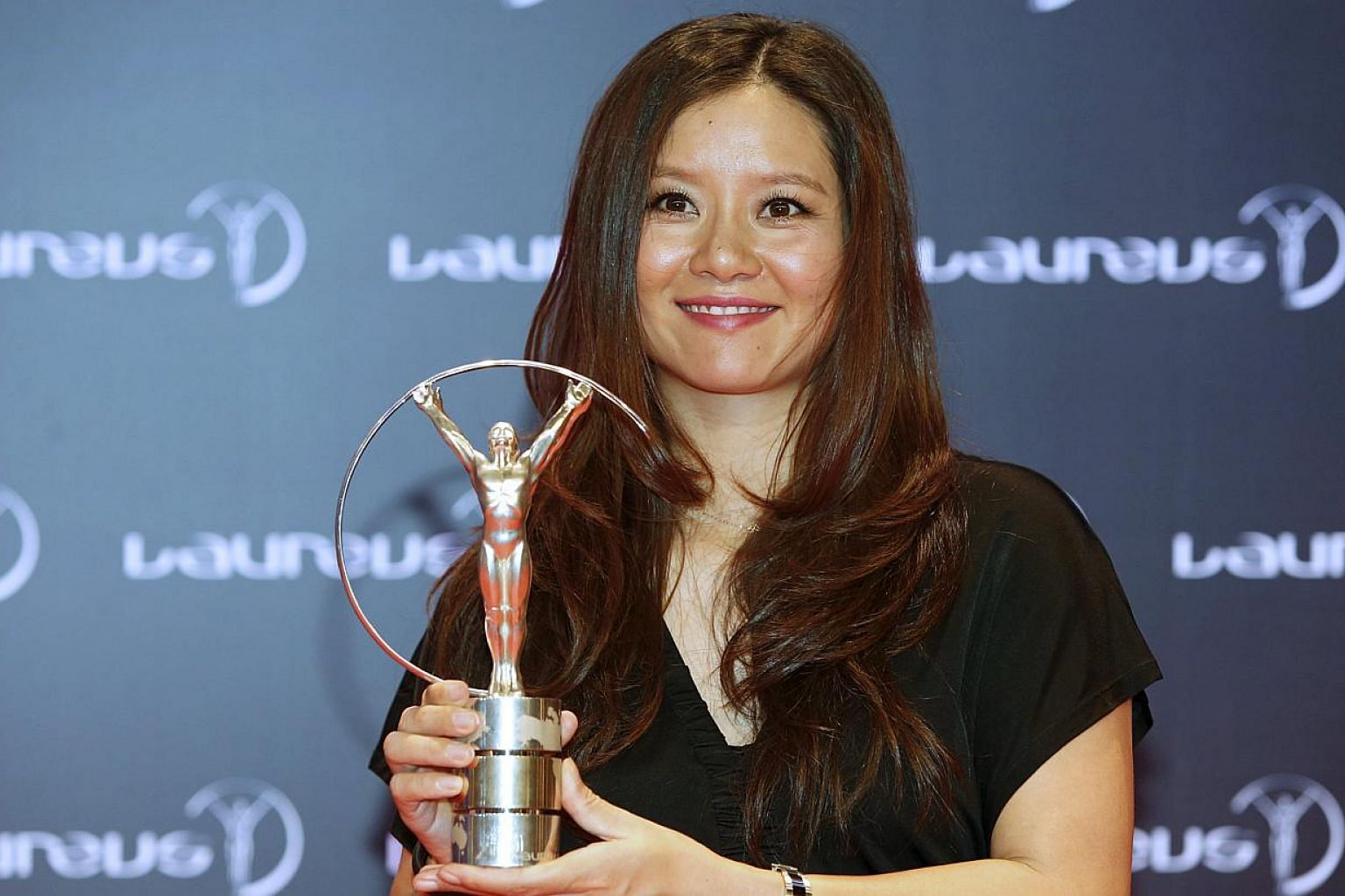 Former tennis player Li Na poses for photographs with her award at the 2015 Laureus World Sports Awards, in Shanghaion April 15, 2015. Retired Chinese tennis star Li Na announced on Wednesday, June 3, that she and her husband have a newborn dau
