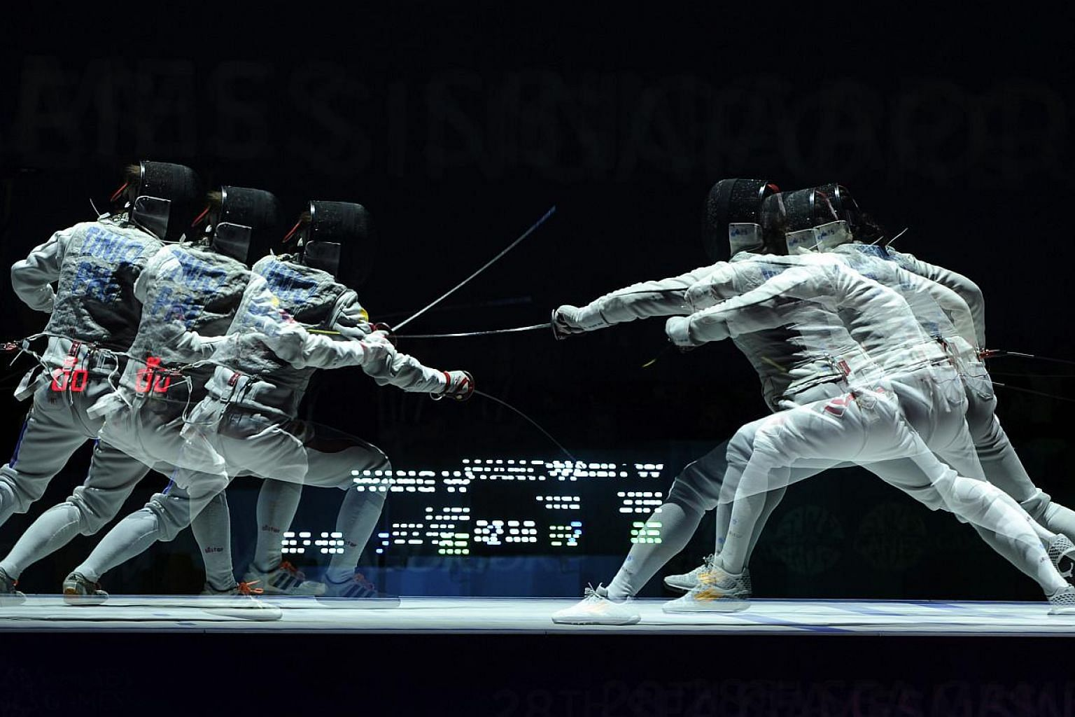 Singapore's Wang Wenying (right) beats Philippines's Justine Gail Tinio (left) 15-7 during the SEA Games fencing Women's individual foil finals held at the OCBC Arena Hall 2 on June 3, 2015. -- PHOTO: REUTERS