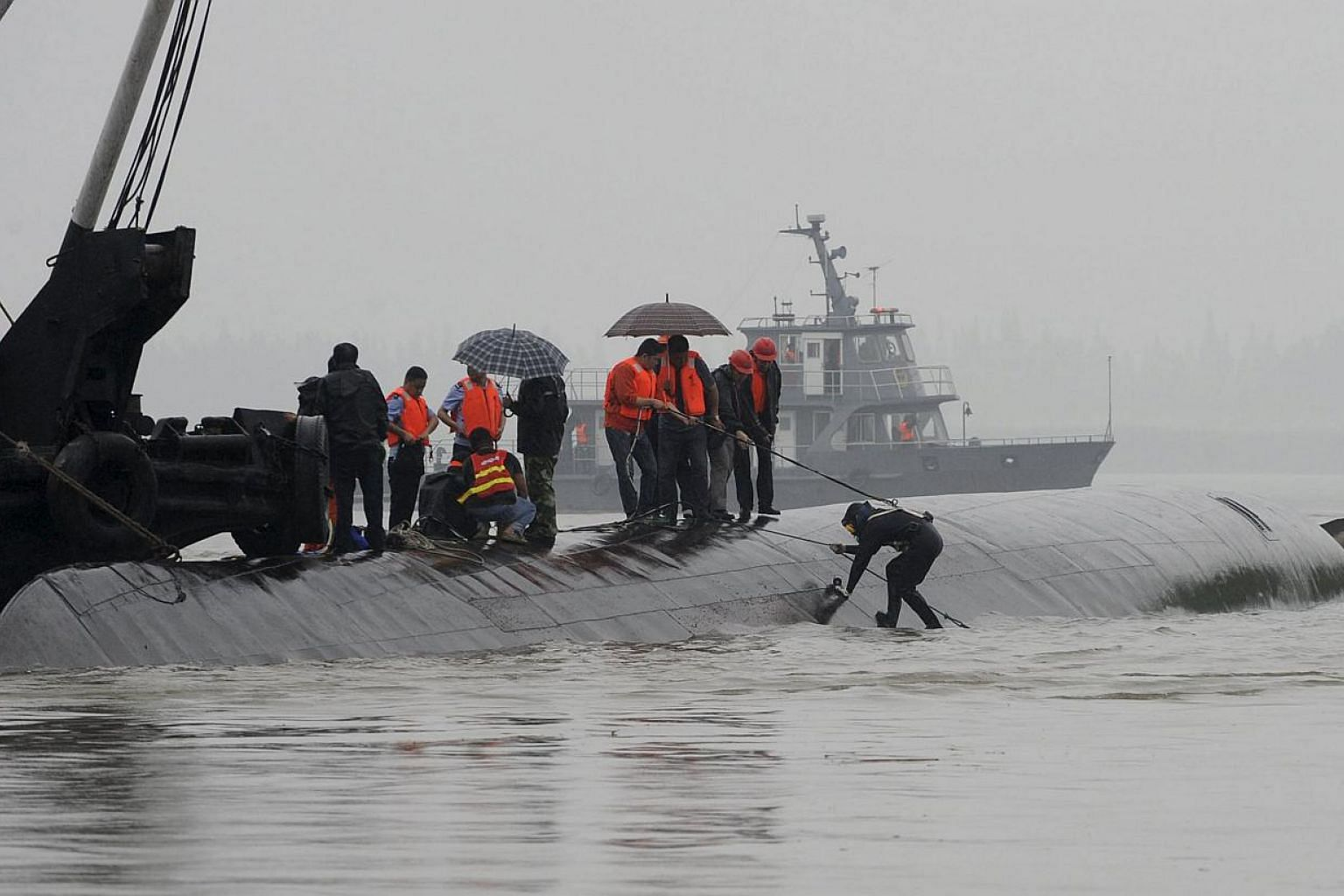 A diver (right) preparing to dive in the river to search for survivors after a ship sank at the Jianli section of the Yangtze River, Hubei province, China, on June 2, 2015. -- PHOTO: REUTERS