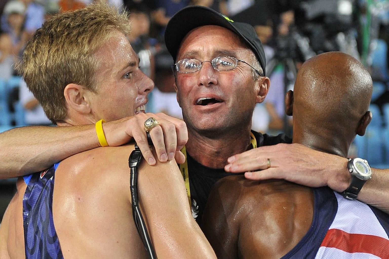 A photograph taken on Sept 4, 2011, shows US coach Alberto Salazar (centre) hugging US athlete Bernard Lagat (right) and US athlete Galen Rupp following the men's 5,000 metres final at the International Association of Athletics Federations (IAAF) Wor