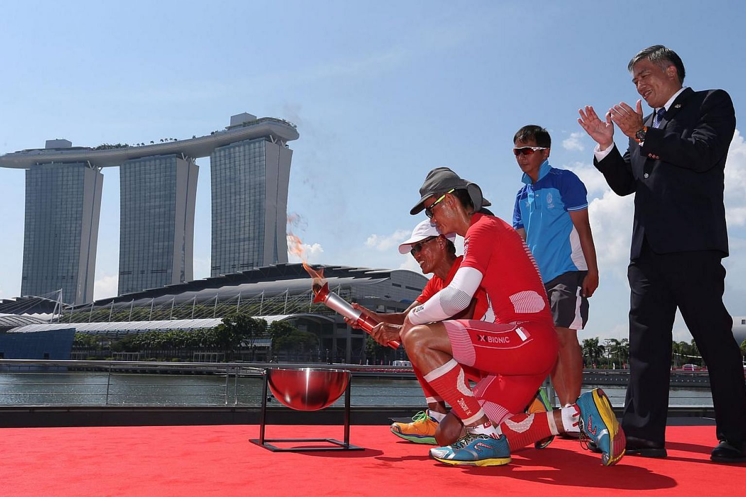 Ultramarathoners Lim Nghee Huat and Yong Yuen Cheng lighting up the official SEA Games torch at The Promontory@Marina Bay. -- PHOTO: REUTERS