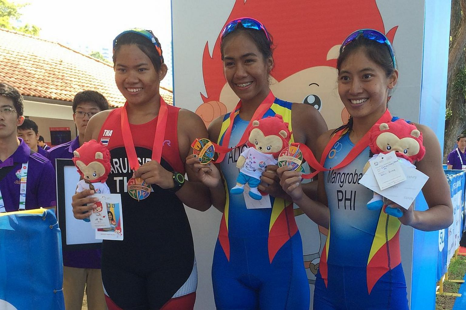 Filipino Maria Claire Adorna (centre) won her country's first gold medal of the SEA Games in the women's triathlonon June 6, 2015. On her right is compatriot and silver medallist Marion Kim Mangrobang, who won silver, while Thailand'sSanr