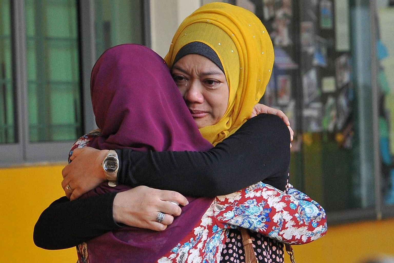 Family members of students from Tanjong Katong Primary School embrace in tears in memory of the victims from the school in an earthquake on Malaysia's Mount Kinabalu. -- PHOTO: AFP