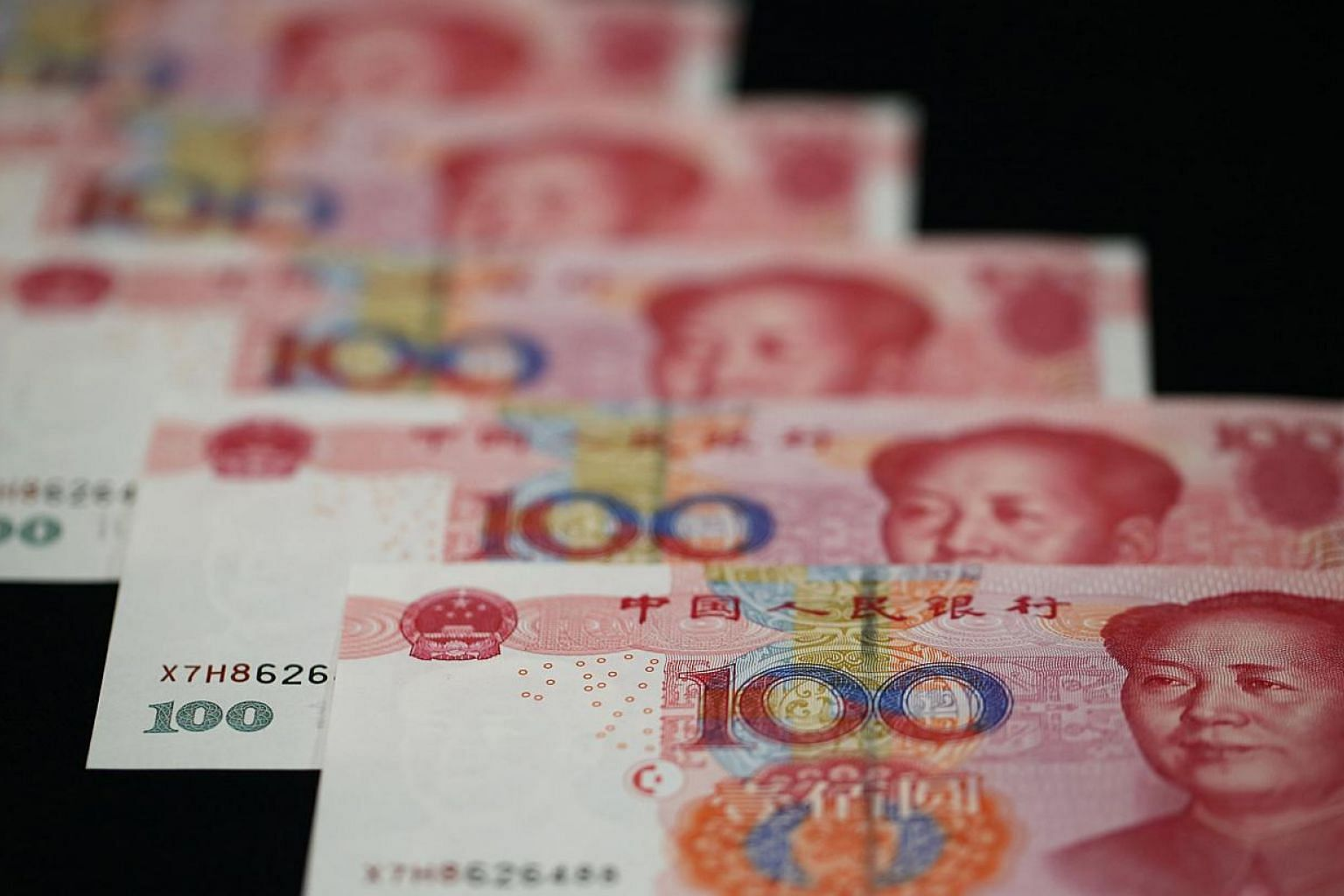 China's yuan inched up against the dollar on Tuesday, after the central bank set the official guidance rate higher. -- PHOTO: BLOOMBERG