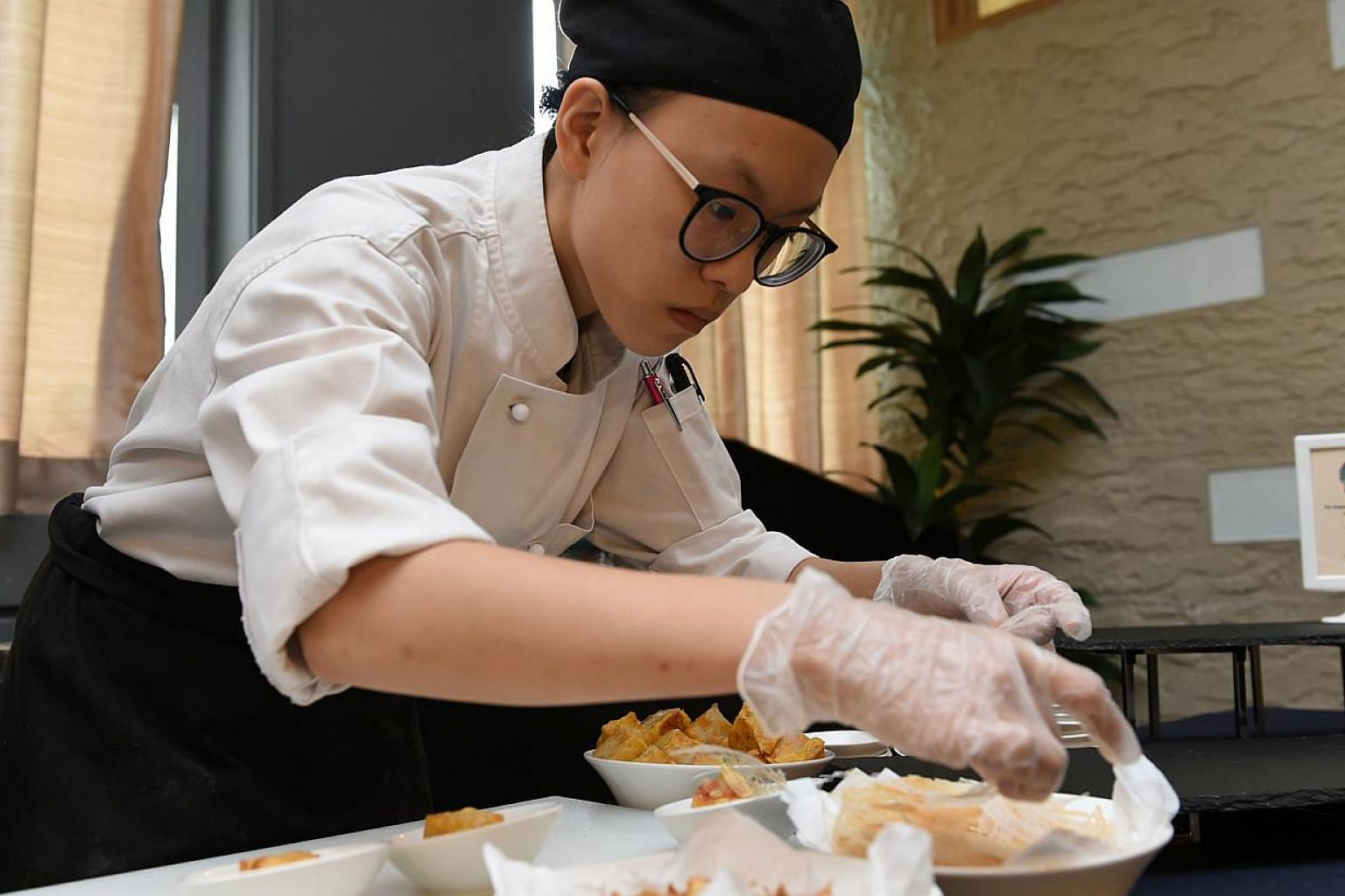 Nanyang Polytechnic student Celine Lee adding the final touches to her reinterpretation of carrot cake at the launch of The Singapore Heritage Cookbook: Past, Present, Future yesterday.