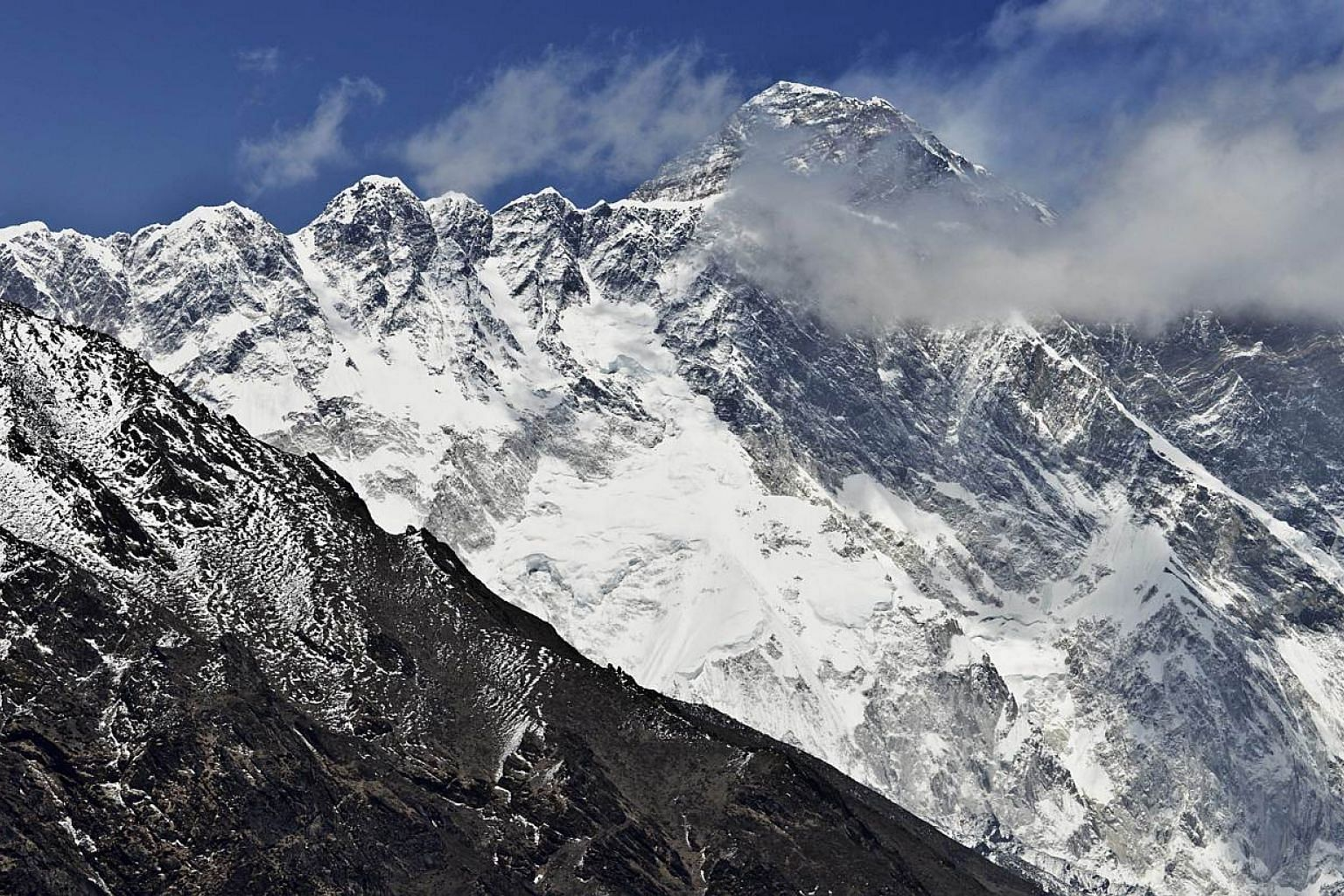 A view of Mount Everest (background) towering over the Nupse-Lohtse massif (foreground) from the village of Tembuche in the Khumbu region of north-eastern Nepal on April 20, 2015. -- PHOTO: AFP