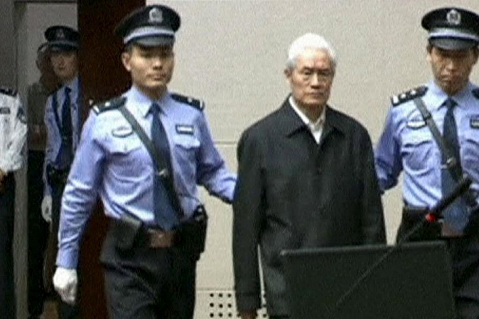 China's former domestic security chief Zhou Yongkang being escorted into court for his sentencing in Tianjin, China, in this still image taken from video provided by China Central Television and shot on June 11, 2015. -- PHOTO: REUTERS