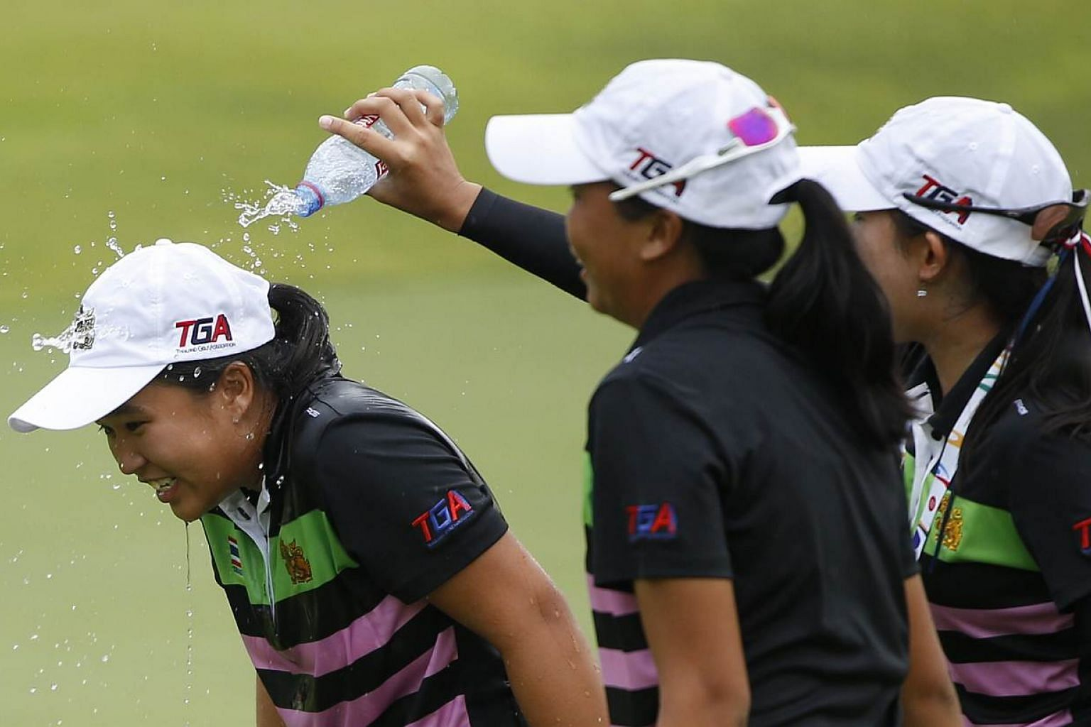 Thailand's Suthavee Chanachai is drenched in water by her teammates after winning the gold medal from the 28th SEA Games golf women's individual at Sentosa Golf course on June 12, 2015.-- ST PHOTO: KEVIN LIM