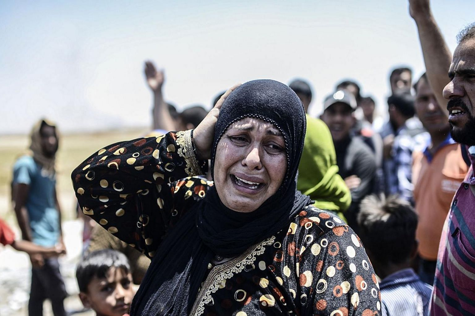 A Syrian woman cries after an airstrike hit the eastern part of the Syrian town of Tal Abyad at the Turkish crossing of Akcakale in the southeast Sanliurfa province on June 14, 2015.Kurdish forces pressed their advance on the strategic militant