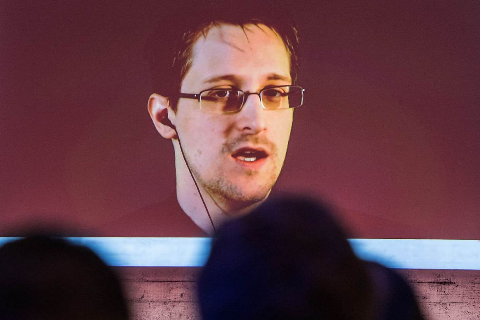 """US National Security Agency (NSA) whistleblower Edward Snowden speaks via live video call during the CeBIT technology fair in Hanover, central Germany, on March 18, 2015. Britain has pulled out agents from live operations in """"hostile countries"""" after"""