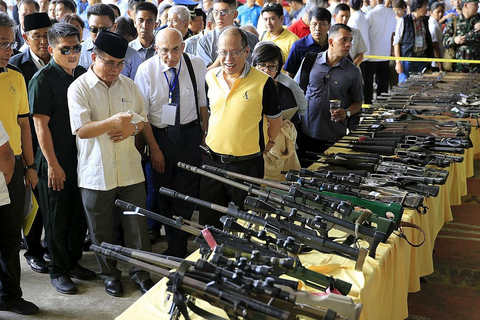 Philippine President Benigno Aquino (front right) and Al-haj Murad Ebrahim (front third right), chairman of the Moro Islamic Liberation Front (MILF), look at weapons during the Ceremonial Turnover of Weapons and Decommissioning of MILF Combatants on