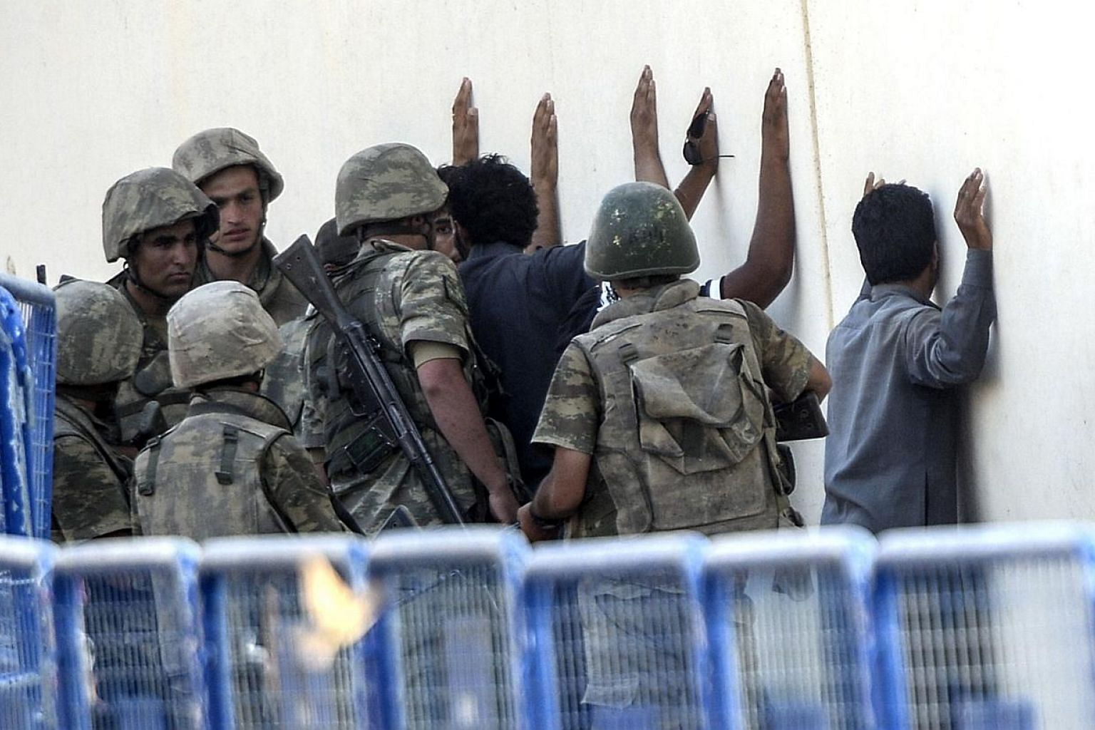 Turkish soldiers detain men who came from Syria and and are said to be ISIS fighters, near the Akcakale crossing gate between Turkey and Syria on Monday. -- PHOTO: AFP