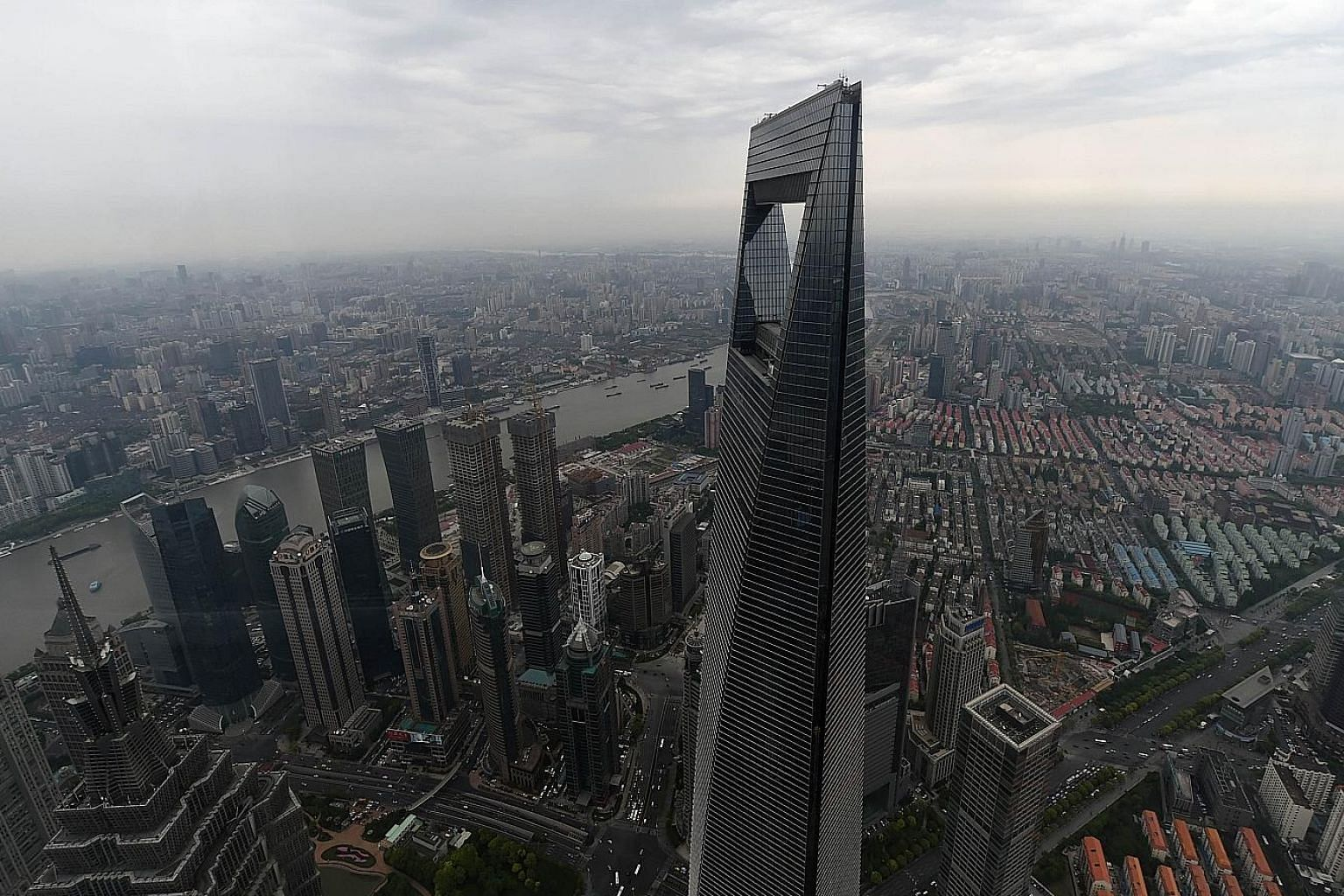 The Shanghai World Financial Centre dominating the skyline of China's financial hub. Chinese stock markets, which had risen as much as 110 per cent from last November to a peak in June, have tumbled more than 20 per cent since June 12.