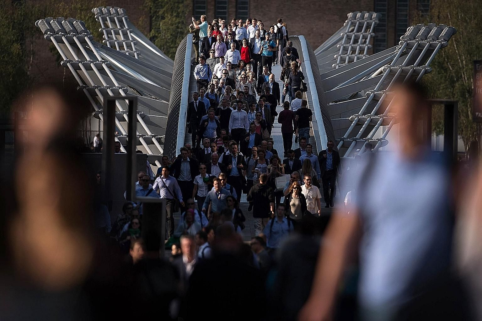 Above: Commuters crossing London's Millennium Bridge as the Tube strike forced many to walk to work. Left: A businessman riding through the centre of the capital to reach his office. Below left: Hundreds queueing for buses at Victoria Station.