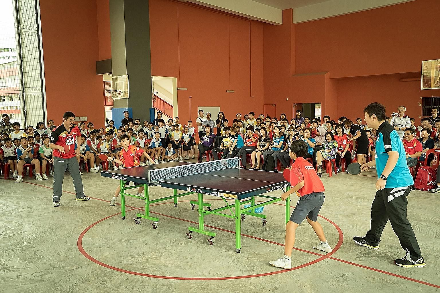 Gao Ning (left, in red jersey) and Li Hu (in blue), men's doubles champions at last month's SEA Games, were among the national table tennis players who spent time at Qi Hua Primary School yesterday. They sparred with pupils and taught them the import