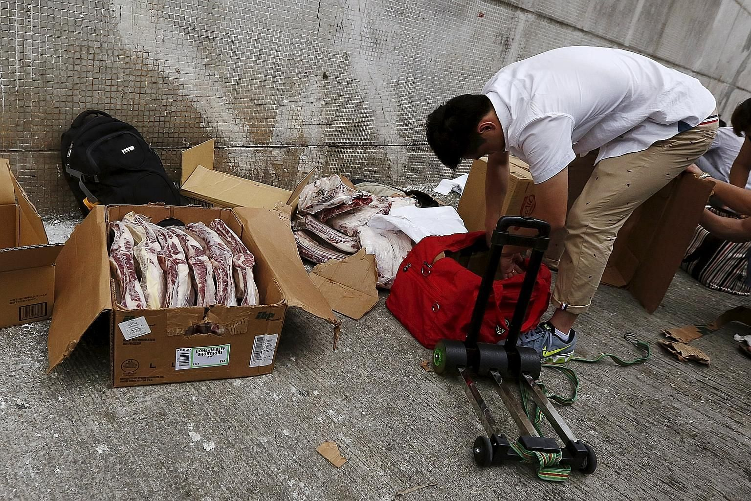 Boxes of frozen beef ribs from the US being unpacked on a side street in a Hong Kong industrial area on Monday, before they are hand-carried and smuggled into mainland China.