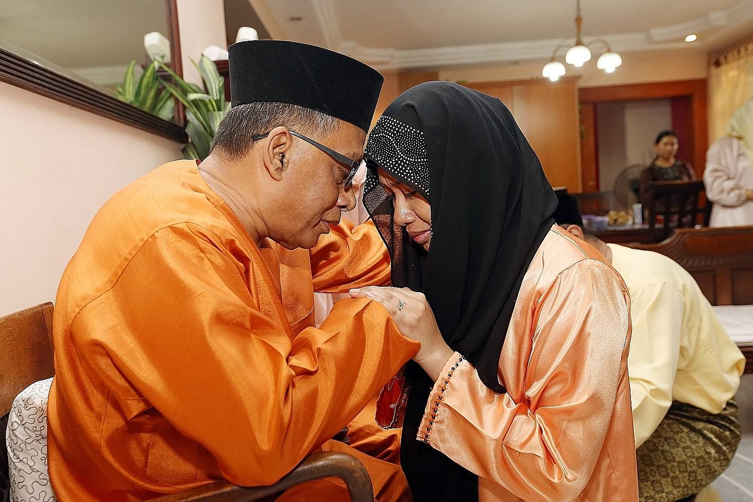 Mr Ismail Awang, 64, embracing daughter-in-law Nur Dayan Danel, 30, as his children and their families asked him and his wife for their forgiveness for any wrongdoing committed in the past year.