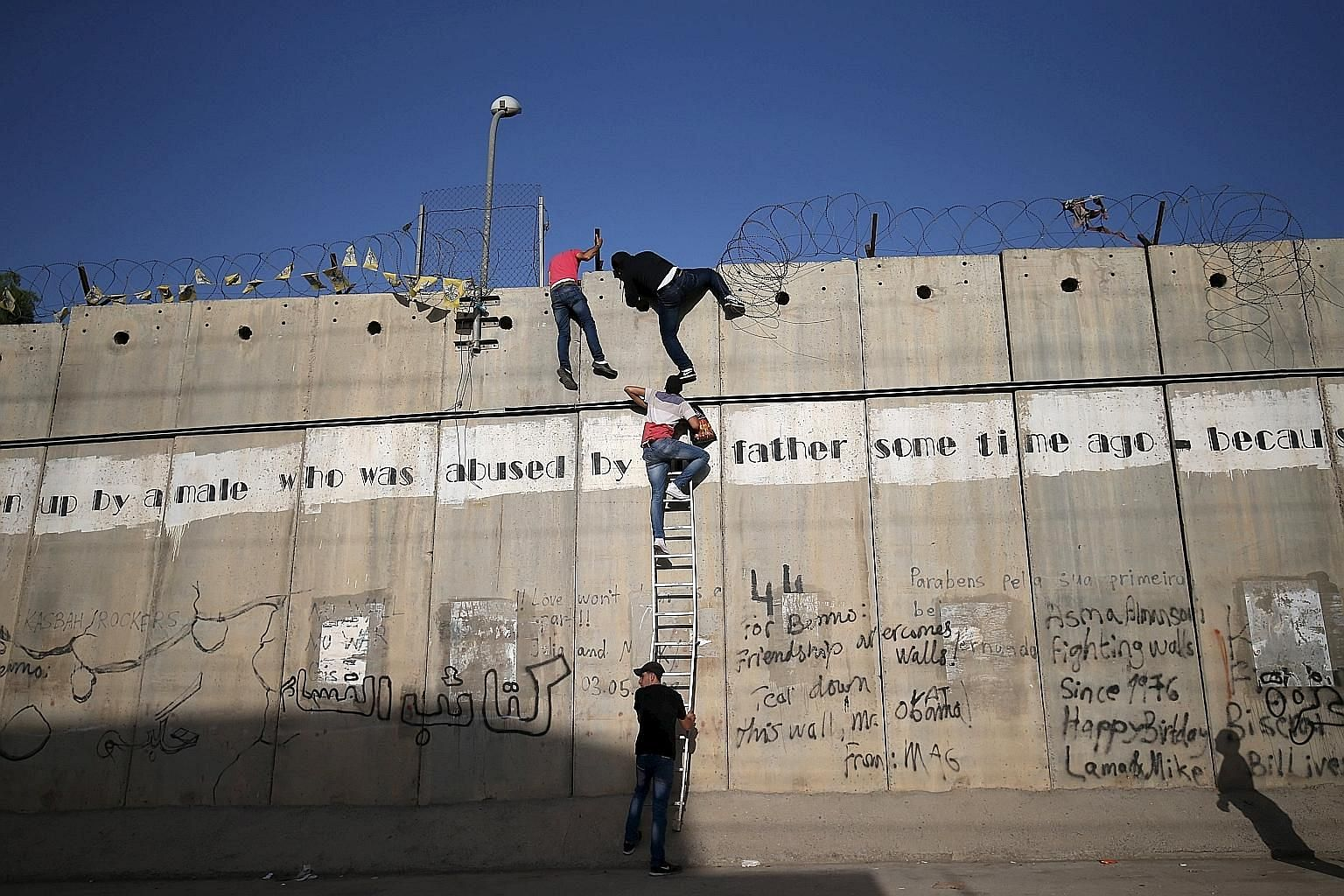 Palestinians scaling a section of the controversial barrier put up by Israel. When the Berlin Wall was torn down a quarter-century ago, there were 16 border fences worldwide. Today, it is said that there are 65 such barriers, either completed or unde