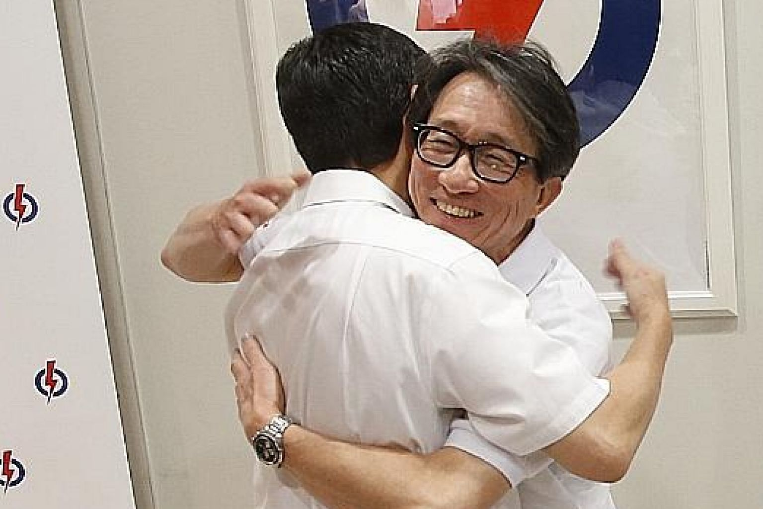 Mr Raymond Lim (left) and Manpower Minister Lim Swee Say hugging each other yesterday.